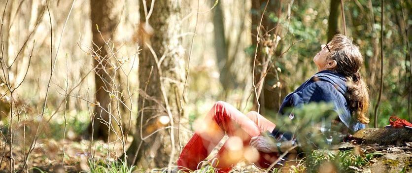 Der Wald ist ein Kraftort: Eine ältere Frau beim Waldbaden.