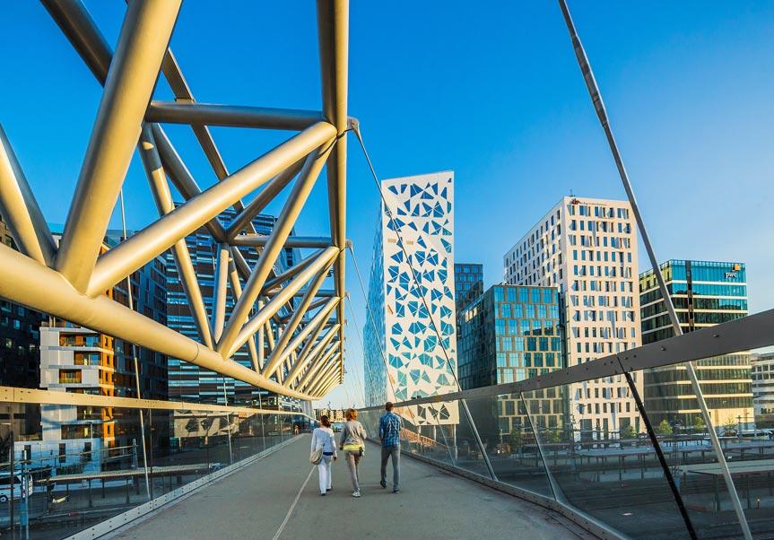 Drei Fussgänger unterwegs auf einer modernen Fussgängerbrücke in Oslo.