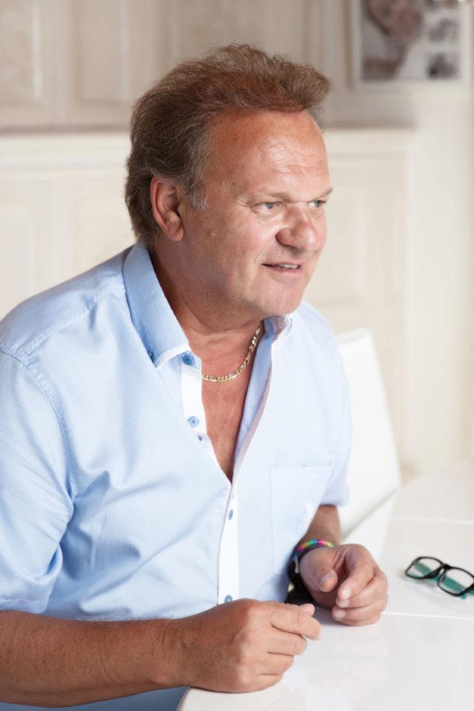 Interviewbild von Musiker Carlo Brunner in seinem Wohnzimmer vor einem weissen Kachelofen.
