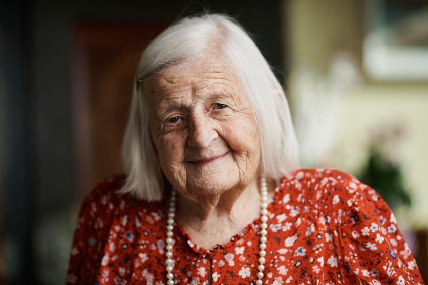 Portrait von Alice Schwegler, 100 Jahre alt. Sie trägt eine Perlenkette und lächelt in die Kamera.