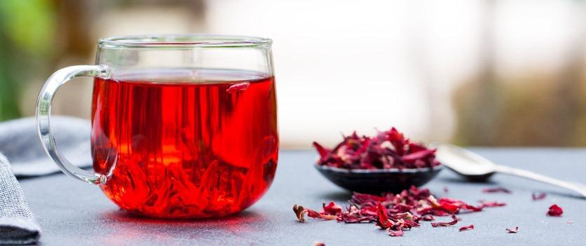 Ein Glas mit rotem Hibiskustee und getrockneten Blüten daneben.