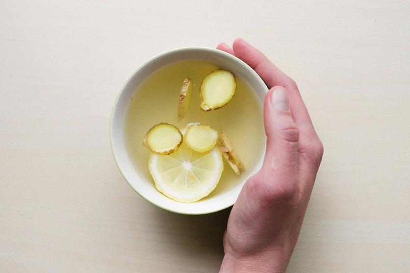 Eine Tasse Ingwertee mit Ingwerscheiben und Zitrone.