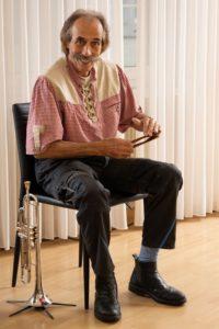 Sigi Michel, mit Löffeln und Trompete.