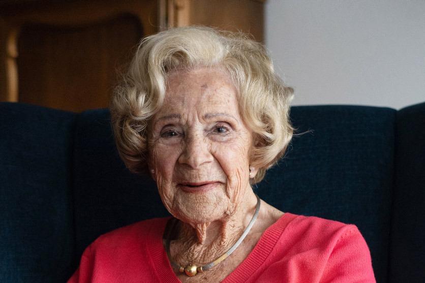 Die 100-jährige Yvonne Hemauer ist im roten Pullover auf dem Sofa und lächelt in die Kamera.