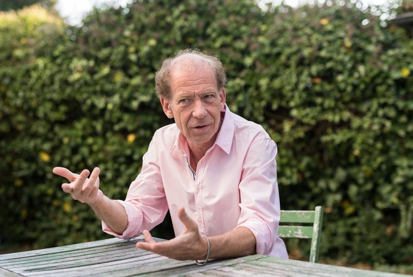 Interviewfoto: Kabarettist Roland Keiser in seinem Garten an einem Gartentisch mit grüner Hecke im Hintergrund.