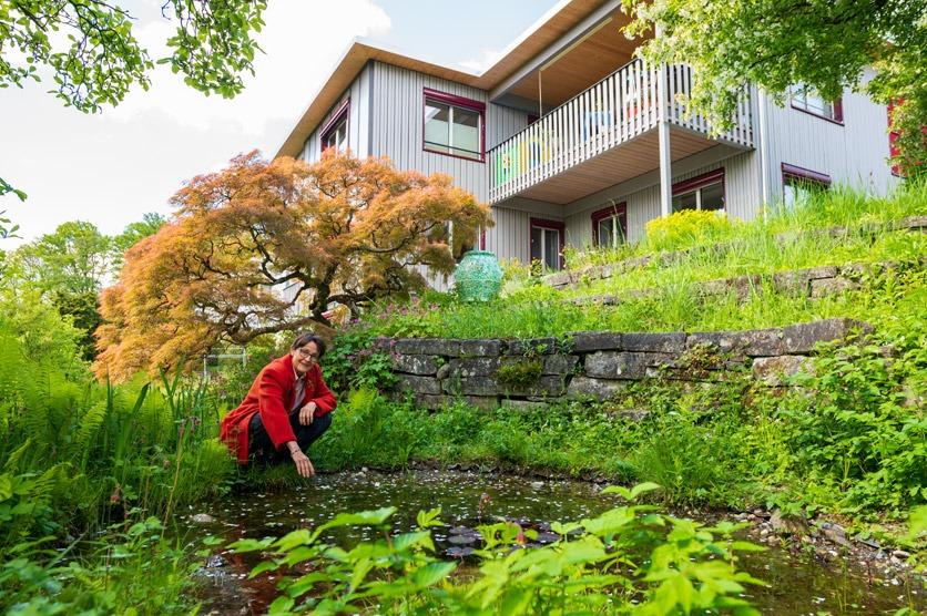 Verena Lubini vor ihrem umgebauten Haus im Garten.