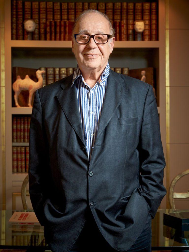 Jean Ziegler steht vor einem Bücherregal, Hände in den Hosentaschen.