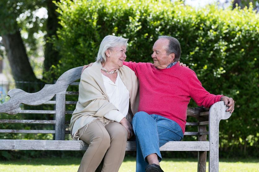Spätes Liebesglück: Helga und Peter sitzen auf einer Bank im Garten und lächeln sich verliebt an.