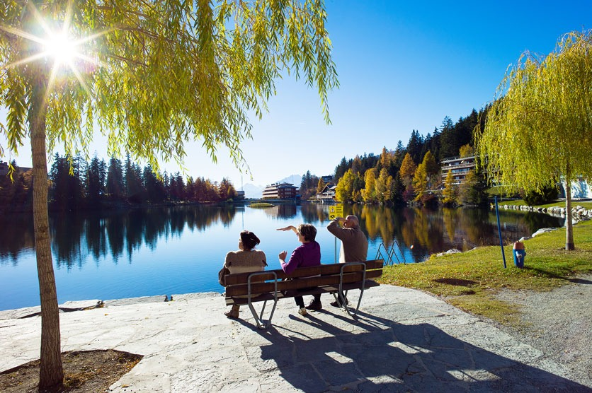 Lac Grenon im herbstlichen Crans-Montana: drei Senioren auf einer Bank geniessen die Aussicht.