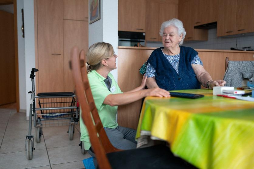 Eine Lernende Fachfrau Gesundheit der Spitex Heitersberg spricht mit einer Klientin unter Aufsicht einer anderen Spitex-Mitarbeiterin (nicht im Bild), am 2. September 2019 in deren Wohnung in Thun, Kanton Mellingen, Kanton Aargau.