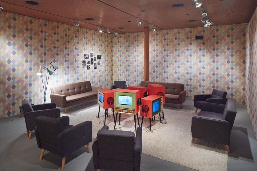 Wohnzimmer mit Retro-Fernsehern und Sesseln.