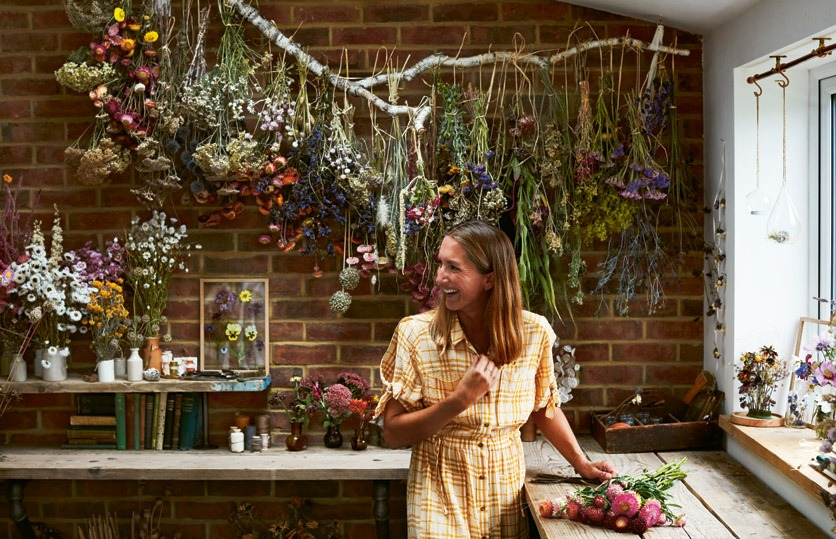 """Bex Partridge, Autorin des Buches """"Trockenblumen"""", in einem Raum mit getrockneten Sträussen an der Wand."""