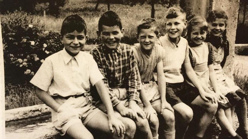 Schwarzweissfoto: sechs Kinder sitzen in einer Reihe auf dem Brunnenrand.