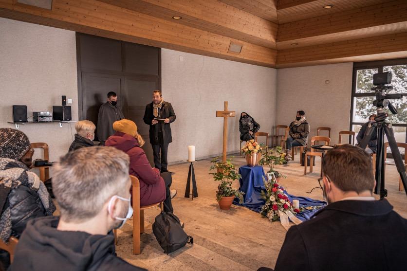 Eine Trauerfeier mit Gästen. Rechts im Bild eine Kamera, die den Ablauf filmt. Zeitlupe.