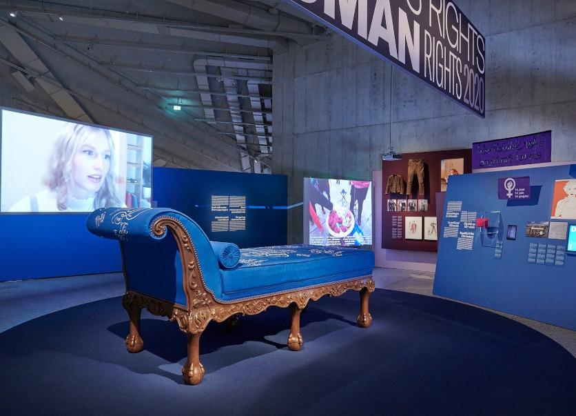 Ausstellungsraum mit einer  blauen Chaiselongue.
