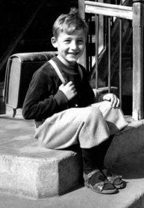 Schwarzweissfoto: ein Schüler mit Thek sitzt auf einer Treppe. Zeitlupe