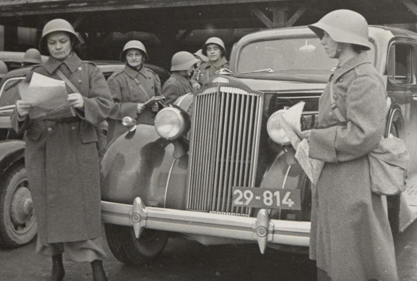 Sanitätsfahrerinnen des FHD, 1939–1945: Frauen in Uniform stehen an einem Fahrzeug..
