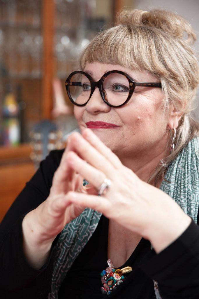 Interviewbild mit Dodo Hug: sie trägt eine schwarze Brille, hochgesteckte Haare und drückt die Fingerspitzen aneinander. Zeiltupe.