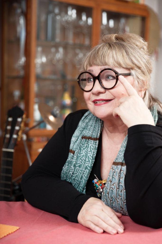 Interviewbild mit Dodo Hug: sie trägt eine schwarze Brille, hochgesteckte Haare. Sie lächelt und ihre Hand berührt den Brillenrand. Zeiltupe.