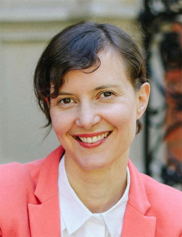 Portrait von Annina Spirig, lächeln im rosa Jacket vor dem Eingang der Pro Senectute