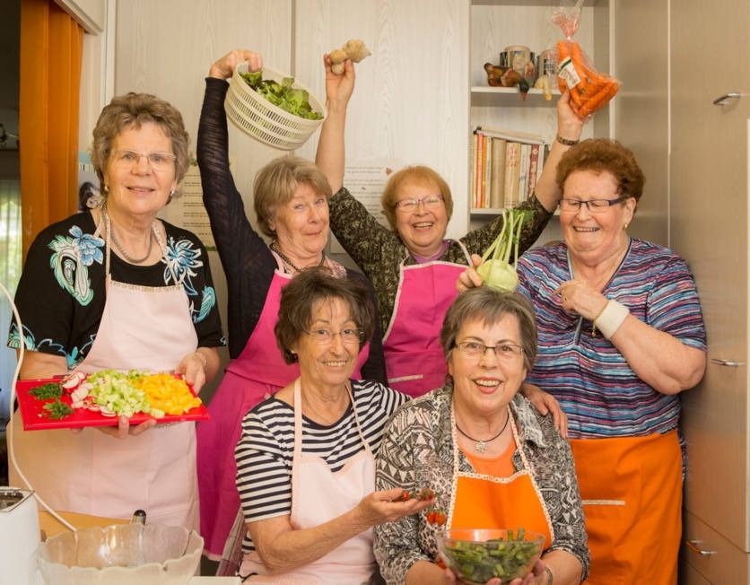 Gruppenfoto mit Seniorinnen in Küchenschürzen und Gemüse in der Hand. Zeitlupe