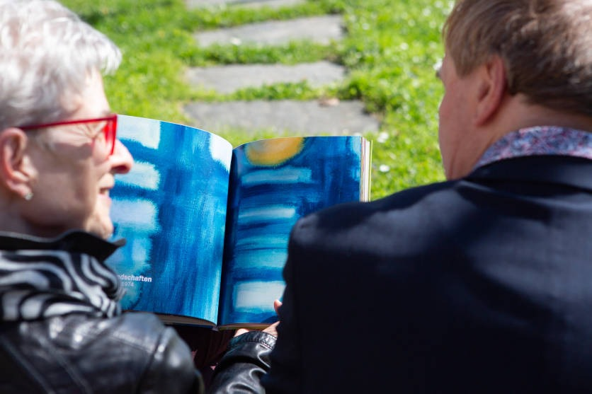 Bernadette Kurmann und ihr geistig beeinträchtigter Bruder Peter schauen zusammen ein Bildband mit seiner Malerei an.