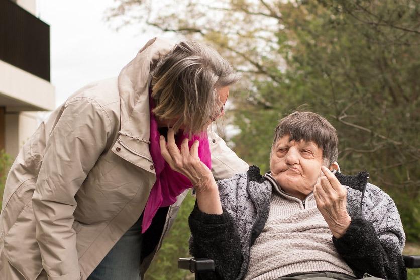 Margrit Wiegand und ihr schwerstbehinderter Bruder Peter. Er streckt ihr seine Hand entgegen um sie zu berühren, sie beugt sich zu ihm herunter.
