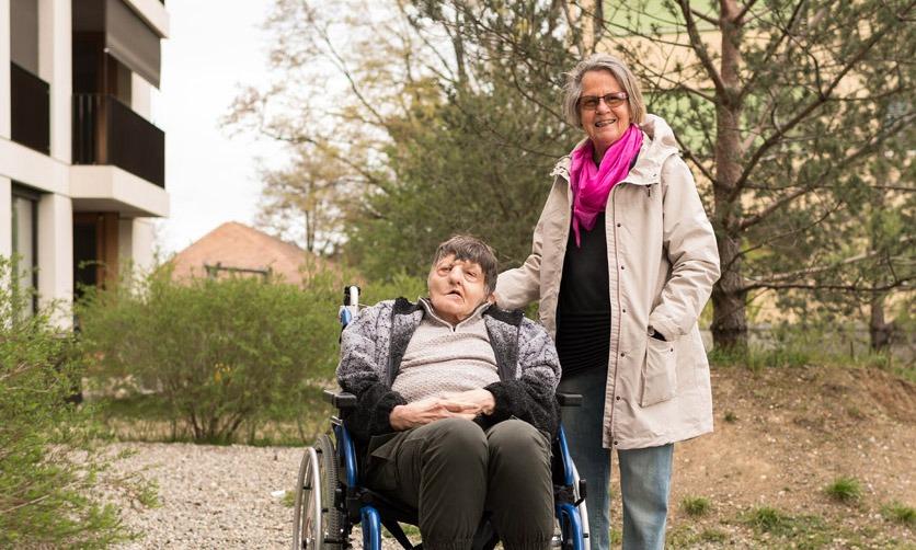 Portrait von Margrit Wiegand und ihrem schwerstbehinderten Bruder Paul Bachmann. Er sitzt im Rollstuhl, im Hintergrund sind Sträucher und Bäume zu sehen.