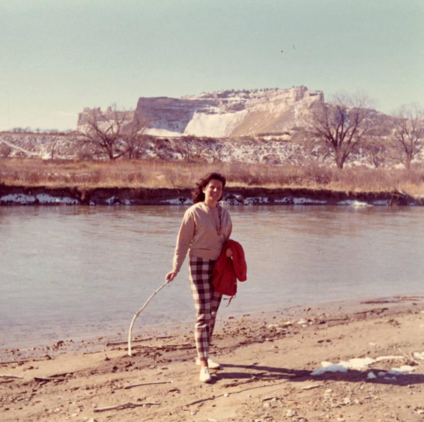 Eine junge Frau steht an einem Flussufer in Nebraska und hält eine rote Jacke und einen Stock in der Hand. Im Hintergrund sind Berge zu sehen. Das Foto wurde in den USA im Frühjahr 1969 aufgenommen.