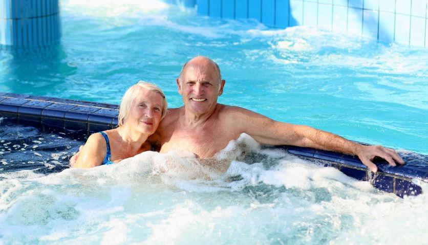 Ein Seniorenpaar sitzt im Sprudelbad und lächelt in die Kamera. Zeitlupe