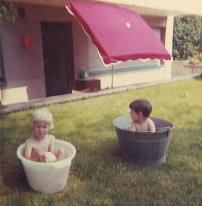 Das waren noch Zeiten: Zwei Kinder in Blechbadewanne und Plastikeimer baden im Garten.