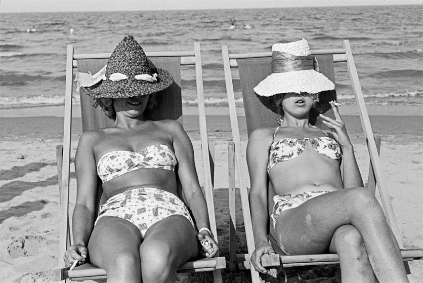 Schwarzweissbild: Zwei Frauen liegen in Liegestühlen am Strand, in Bikinimode der 1960er Jahre, mit Hüten tief ins Gesicht gezogen.