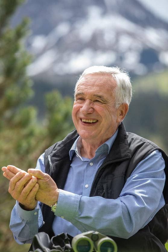 Hanspeter Latour lacht und gestikuliert, auf dem Tisch liegt ein Fernglas, im Hintergrund sind unscharf Berge zu erkennen.