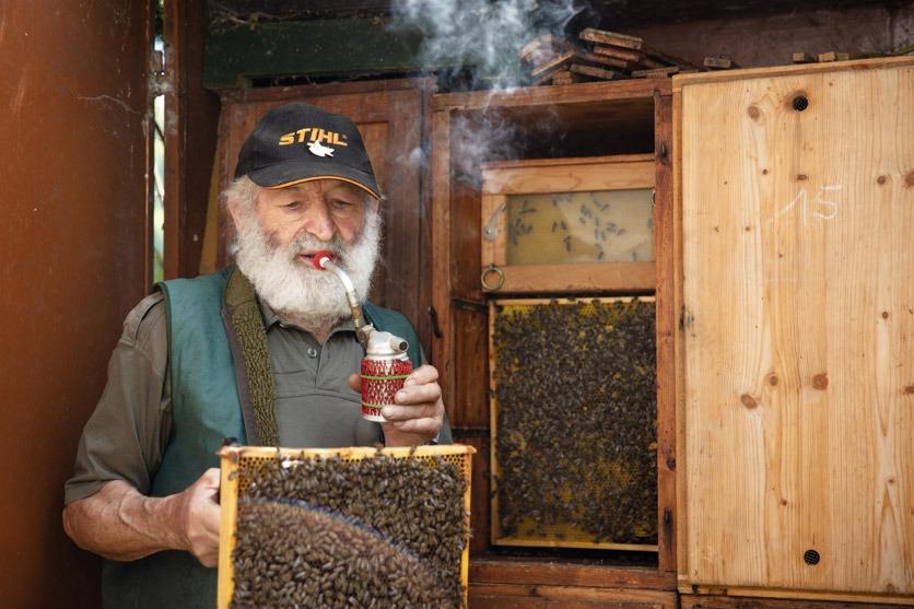 Hobby-Imker Ernst Leuenberger mit einer Pfeife, deren Rauch die Bienen beruhigen soll.