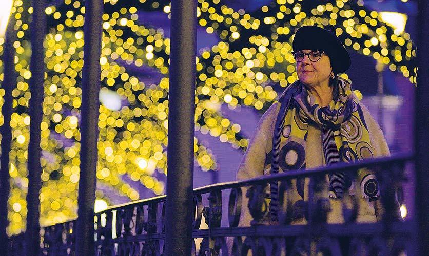 Eine Frau steht alleine auf einer Brücke, im Hintergrund ist eine Weihnachtsbeleuchtung zu sehen.