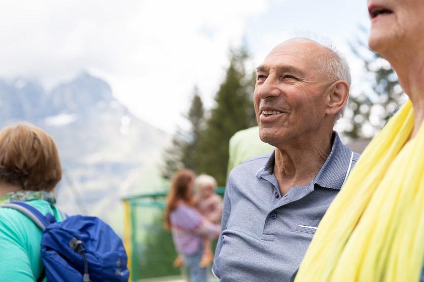 Ein Senior lacht im Gespräch mit anderen älteren Personen.