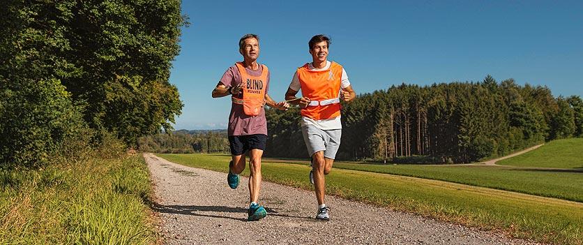Ein Freiwilliger des Netzwerkes UBS Helpetica joggt mit einem blinden Sportler.