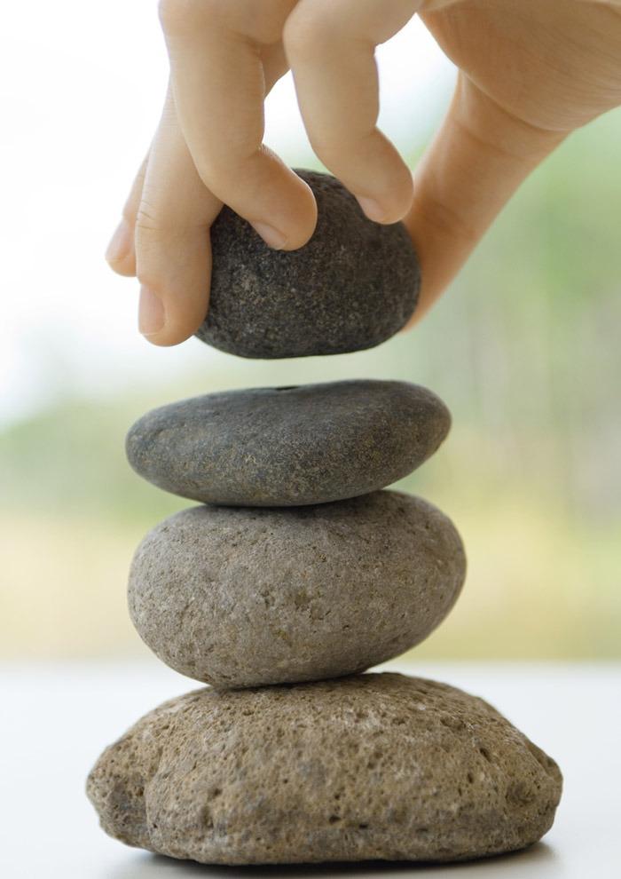 """Symbolisch für """"Das vierte Alter"""": eine Hand legt einen vierten Stein auf einen bestehenden Dreierstapel."""
